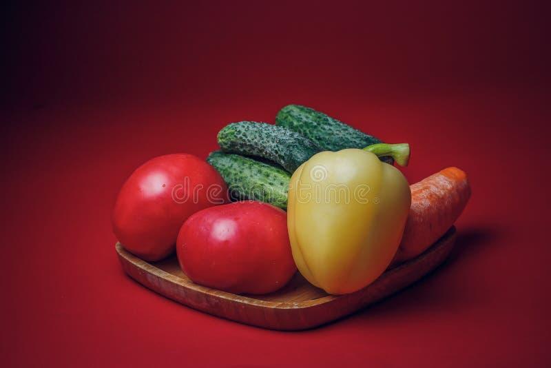 Verdura fresca messa su un piatto di bambù su fondo rosso fotografia stock libera da diritti