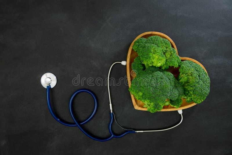 Verdura verde del bróculi en placa de madera como corazón foto de archivo