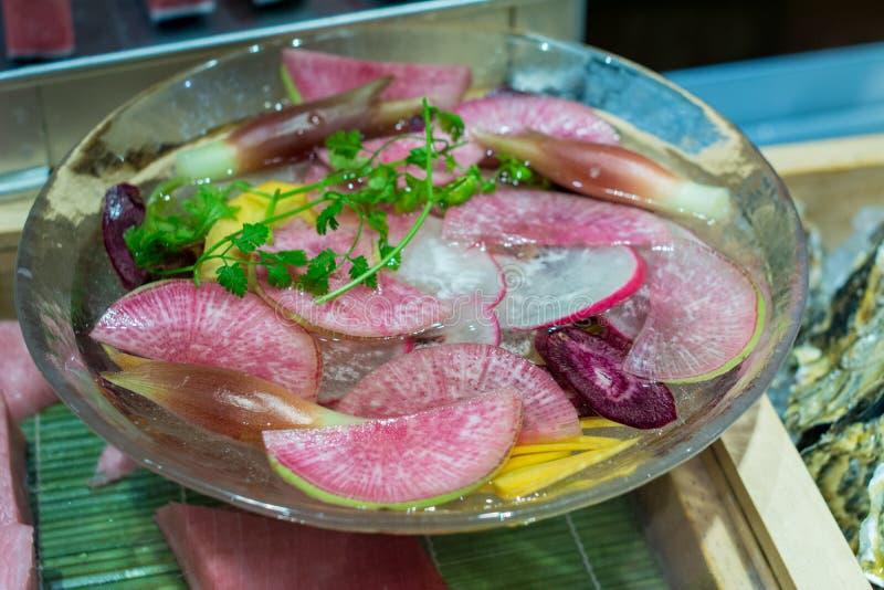 Verdura y jengibre conservados en vinagre mezclados con agua en bol de vidrio fotografía de archivo