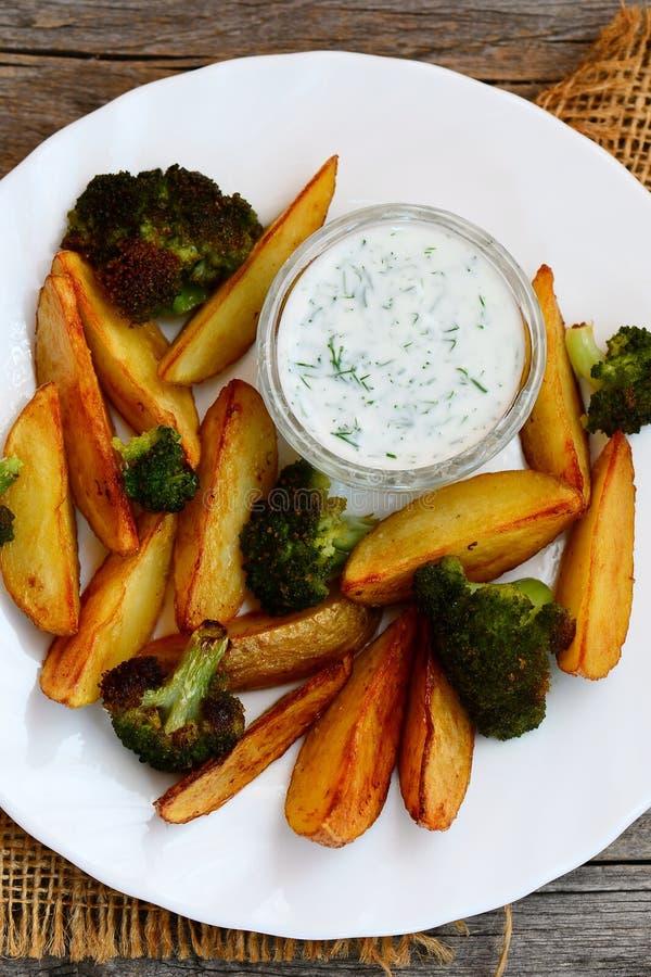 Verduras asadas horno Patatas cocidas con la salsa del bróculi y de crema agria Comida vegetariana fácil y sana Foto vertical tap foto de archivo libre de regalías