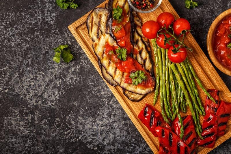 Verduras asadas a la parrilla con la salsa de tomate y las hierbas frescas fotos de archivo