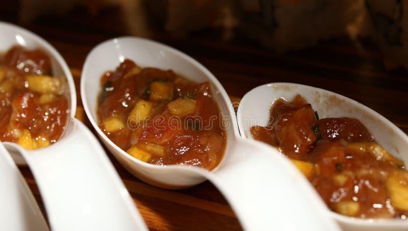 Verduras asiáticas con la salsa marrón adentro con las cucharas fotos de archivo
