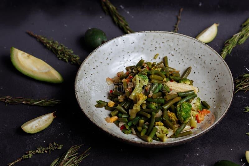 Verduras cocidas bróculi, maíz, habas en una placa en un fondo negro con el aguacate y cal fotografía de archivo libre de regalías