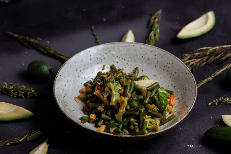 Verduras cocidas br?culi, ma?z, habas en una placa en un fondo negro con el aguacate y cal imagen de archivo libre de regalías