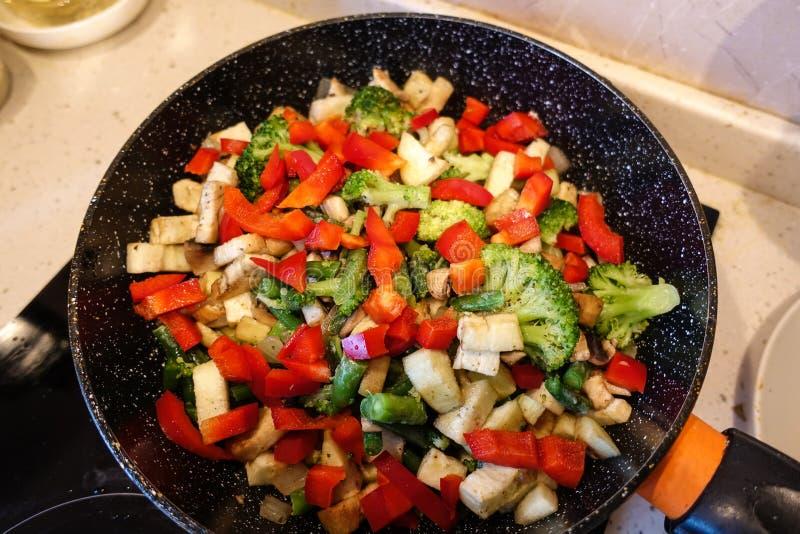 Verduras cocinadas en una cacerola Proliferan r?pidamente los champi?ones, br?culi, paprika Comida vegetariana El concepto de con imágenes de archivo libres de regalías