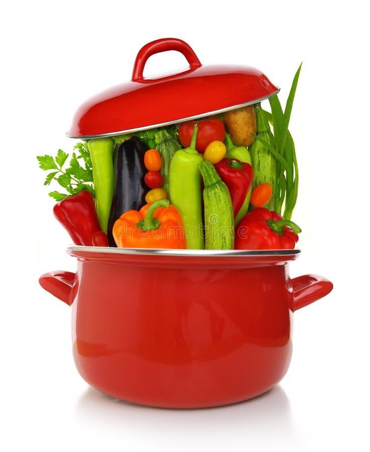 Verduras coloridas en un pote de cocinar rojo fotos de archivo
