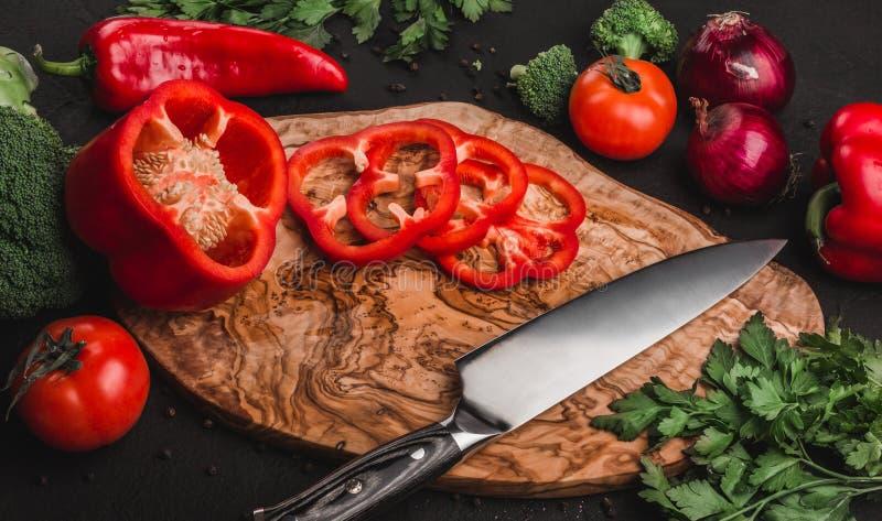 Verduras con el cuchillo en tabla de cortar sobre el fondo de piedra, cocinando la comida Ingredientes en la tabla fotografía de archivo libre de regalías