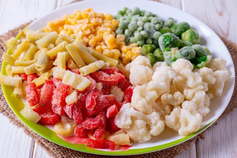 Verduras congeladas en una coliflor del cuenco, coles de Bruselas, guisantes, pimientas, maíz, calabacín, habas verdes imagen de archivo libre de regalías