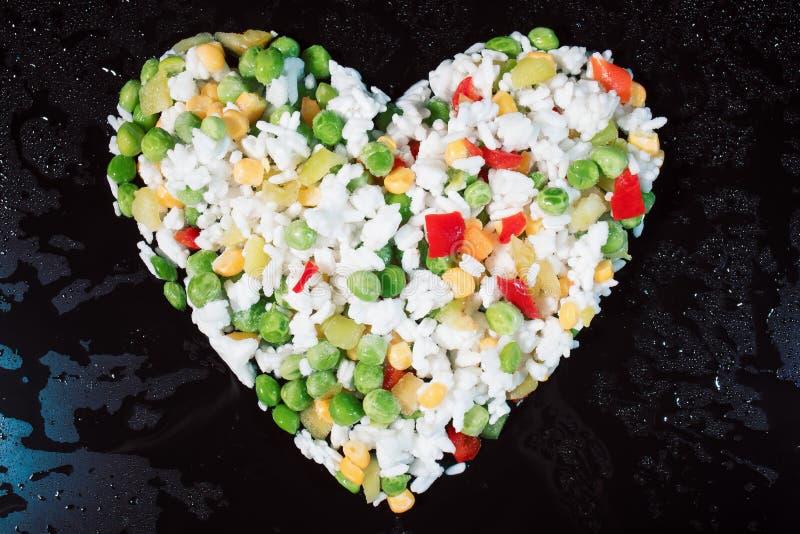 Verduras congeladas multicoloras en la forma del corazón en un fondo negro imagen de archivo
