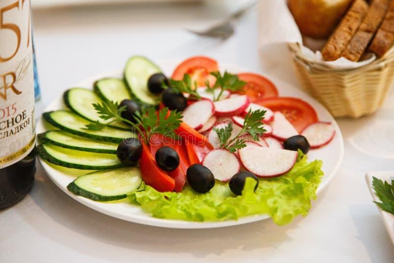 Verduras cortadas maravillosamente en un plato blanco Pepino, tomate rojo, paprika rojo, aceitunas, rábano, del perejil de la hoj imágenes de archivo libres de regalías