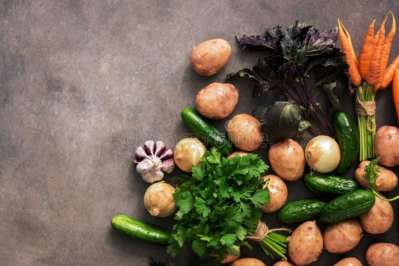 Verduras crudas frescas de la nuevos cosecha, patatas, cebollas, zanahorias, ajo, pepinos, albahaca y perejil en un fondo rústico foto de archivo