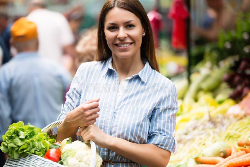 Verduras de compra de la mujer joven en el mercado fotos de archivo libres de regalías