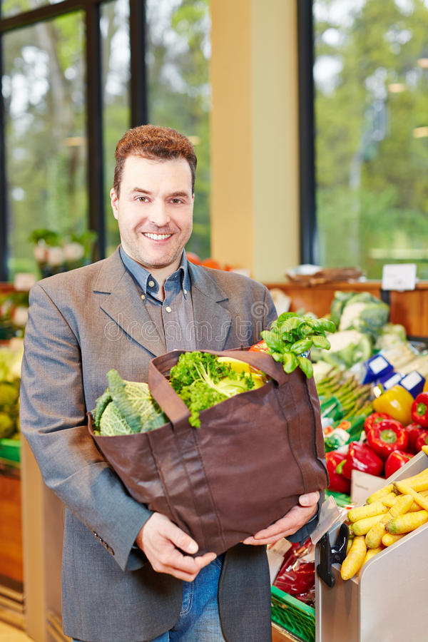 Verduras de compra sonrientes del hombre en supermercado fotografía de archivo libre de regalías