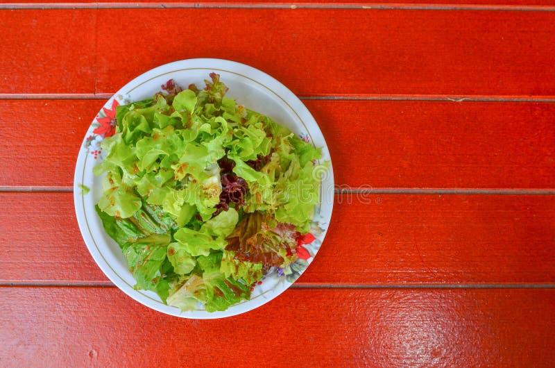 Verduras de ensalada en un plato en un piso de madera rojo imagen de archivo libre de regalías