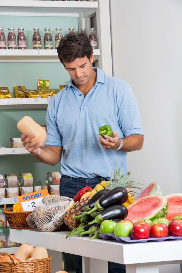 Verduras de las compras del hombre en supermercado imagenes de archivo