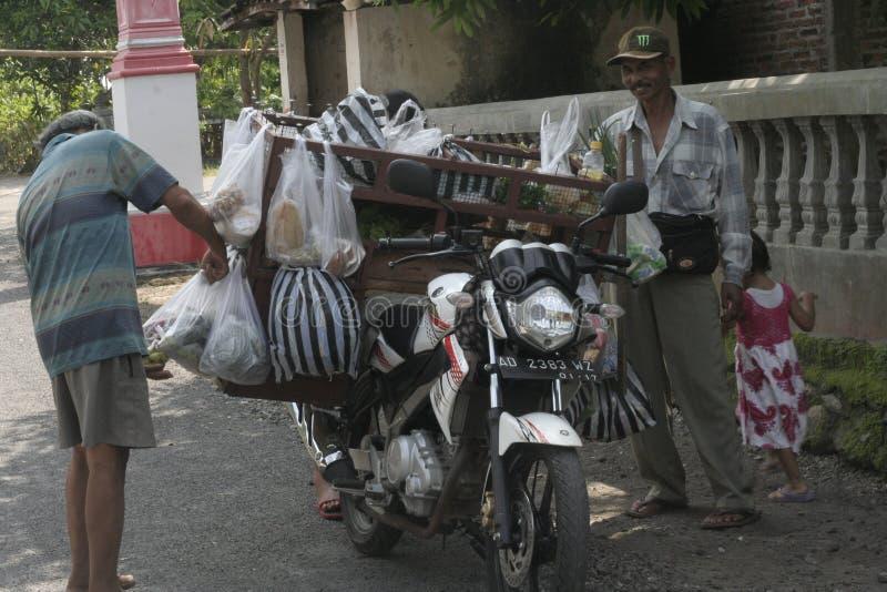 VERDURAS DE LOS COMERCIANTES USANDO VIAJE DE LA MOTOCICLETA foto de archivo libre de regalías