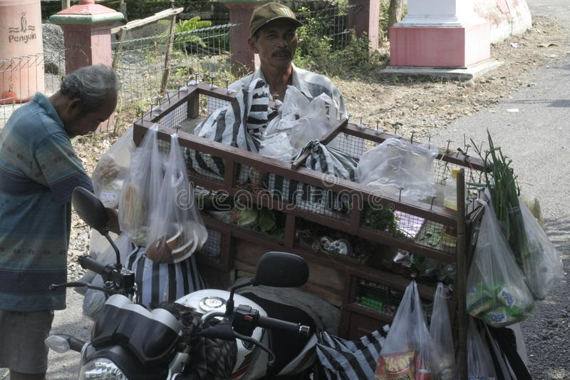 VERDURAS DE LOS COMERCIANTES USANDO VIAJE DE LA MOTOCICLETA imagen de archivo libre de regalías