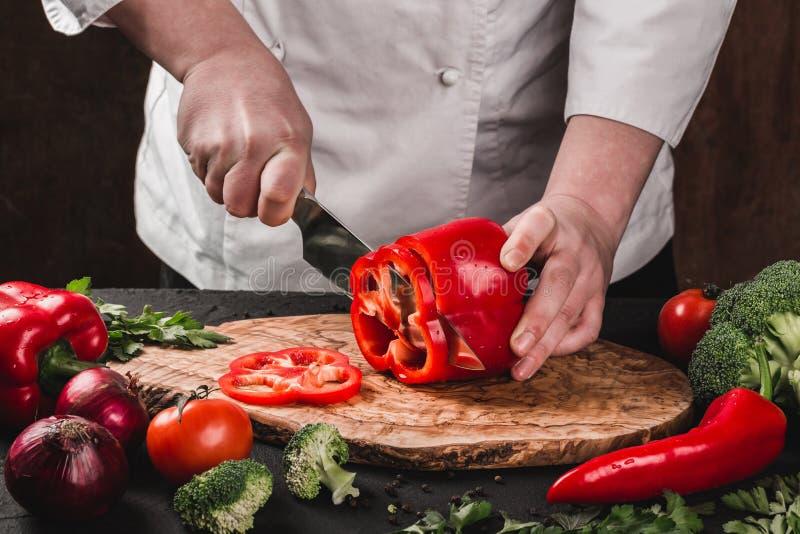 Verduras del corte del cocinero con el cuchillo en la cocina, cocinando la comida Ingredientes en la tabla imagenes de archivo