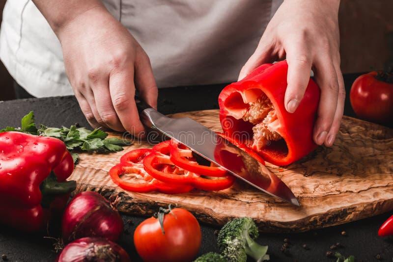 Verduras del corte del cocinero con el cuchillo en la cocina, cocinando la comida Ingredientes en la tabla fotos de archivo libres de regalías