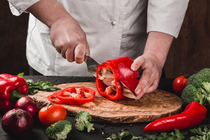 Verduras del corte del cocinero con el cuchillo en la cocina, cocinando la comida Ingredientes en la tabla imagen de archivo