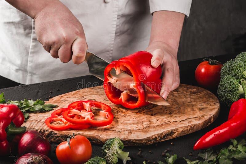 Verduras del corte del cocinero con el cuchillo en la cocina, cocinando la comida Ingredientes en la tabla Concepto sano del alim fotografía de archivo