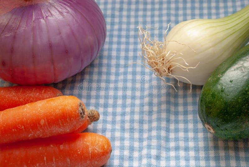 Verduras en el paño a cuadros azul y blanco de la cocina imagenes de archivo