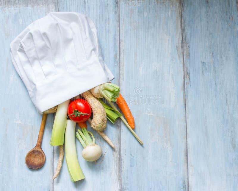Verduras en el sombrero del cocinero que cocinan el extracto de la comida foto de archivo
