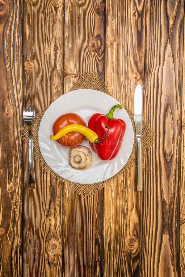 verduras en la placa una tabla de madera imagenes de archivo