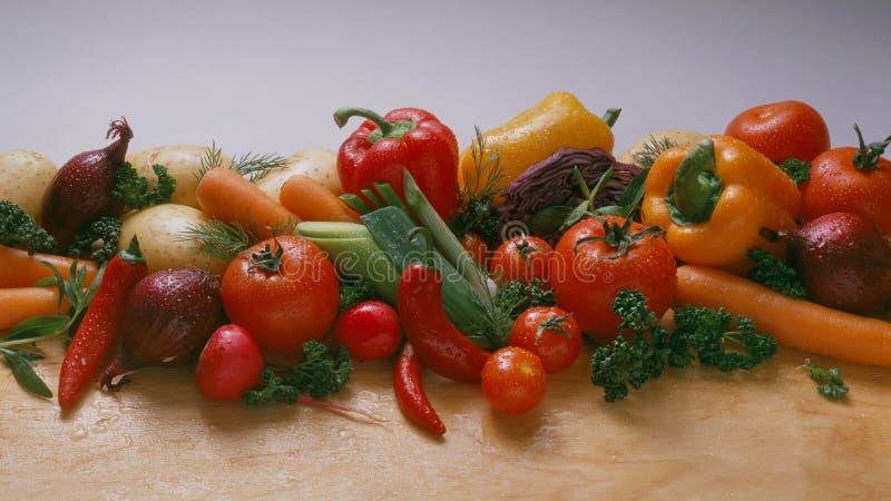 Verduras - en un fondo ligero, en un de madera la tabla: tomates, tomates de cereza en una rama, zanahorias, cebolla roja foto de archivo