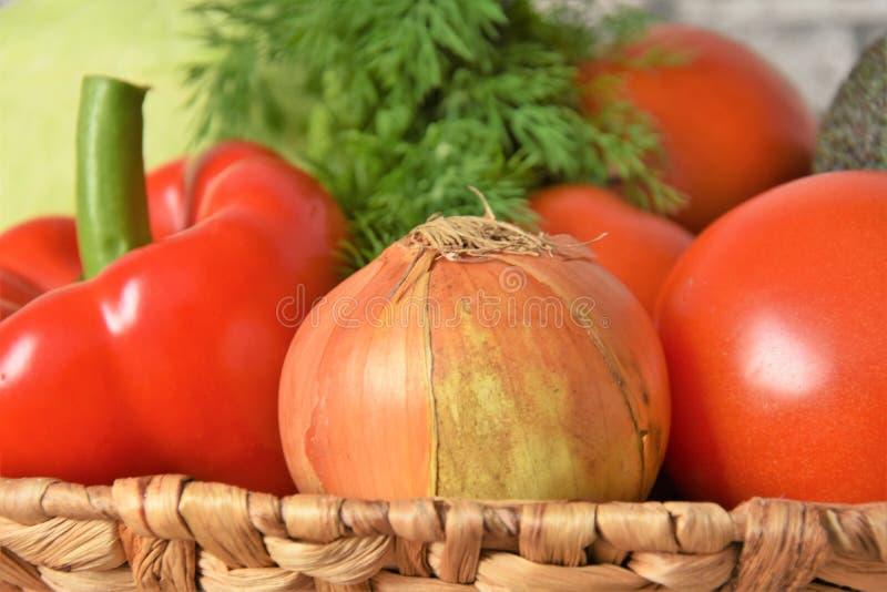 Verduras enteras en una cesta de mimbre fotos de archivo