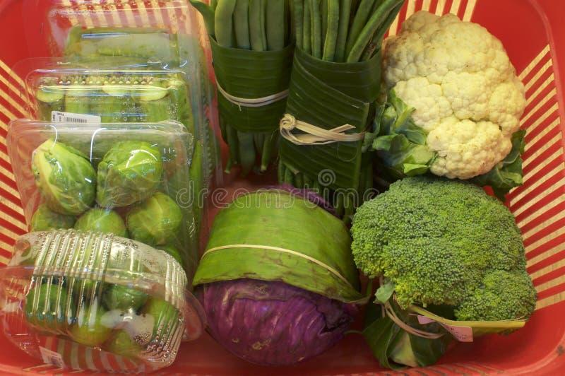 Verduras envueltas en hojas del pl?tano contra Envase de pl?stico imagen de archivo libre de regalías