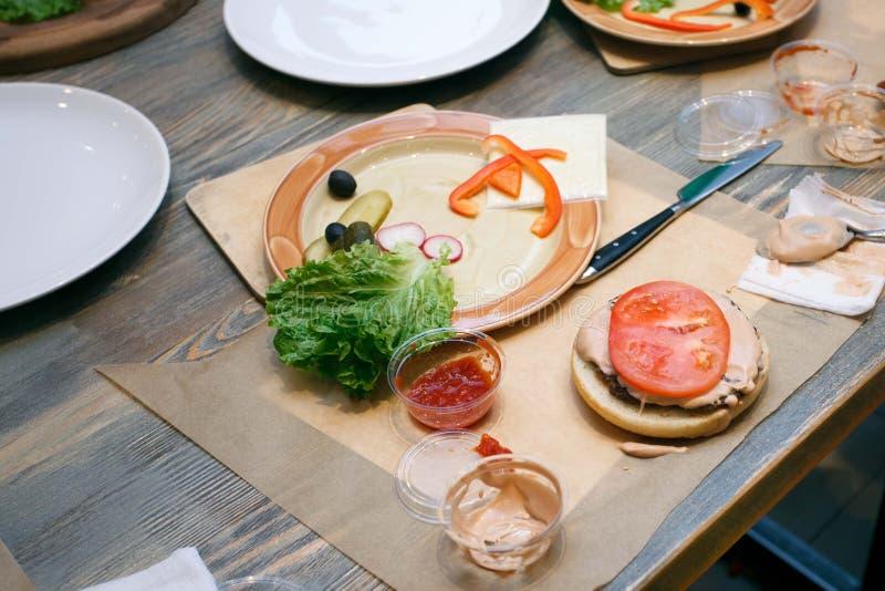 Verduras frescas, bollo de hamburguesa y utensilios para las clases de cocina en la tabla de madera, concepto de clase de cocina imágenes de archivo libres de regalías