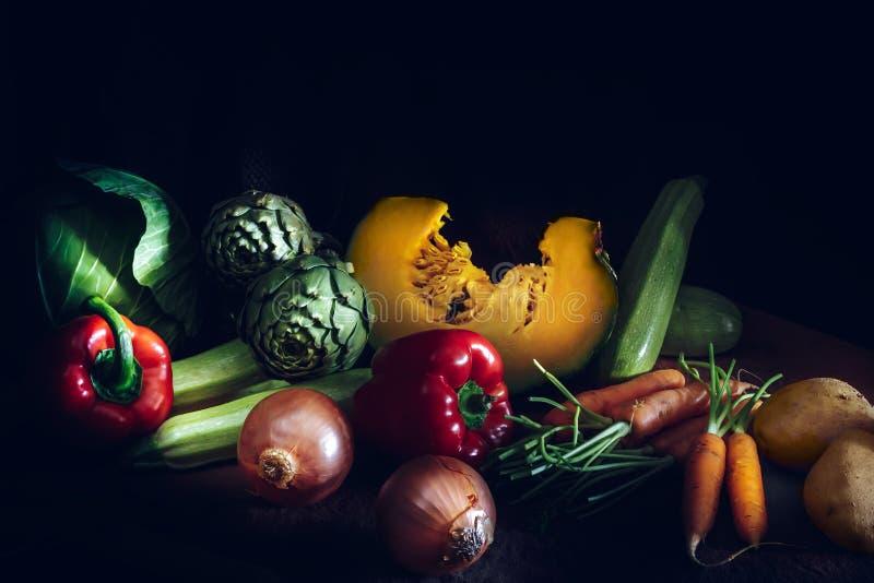Verduras frescas coloridas en fondo negro Zanahorias, col, fotografía de archivo