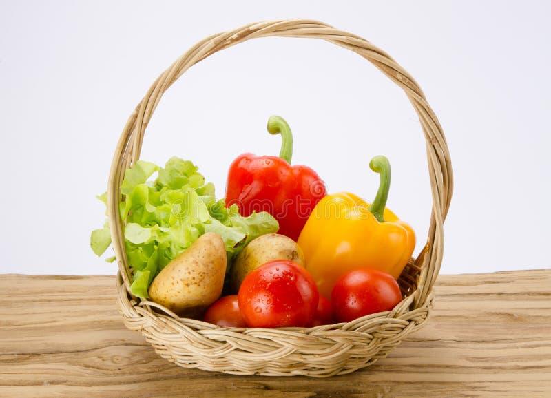 Verduras frescas en cesta en el escritorio de madera fotos de archivo