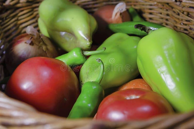 Verduras frescas en el cierre de la cesta de mimbre. Pimienta agarrada, tomate, pimienta picante, cebolla, zanahoria foto de archivo
