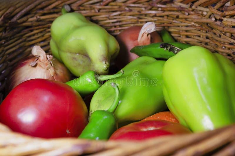 Verduras frescas en el cierre de la cesta de mimbre. Pimienta agarrada, tomate, pimienta picante, cebolla, zanahoria fotografía de archivo libre de regalías