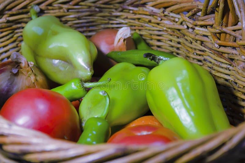 Verduras frescas en el cierre de la cesta de mimbre. Pimienta agarrada, tomate, pimienta picante, cebolla, zanahoria fotos de archivo libres de regalías