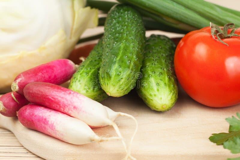 Verduras frescas en el panel duro foto de archivo