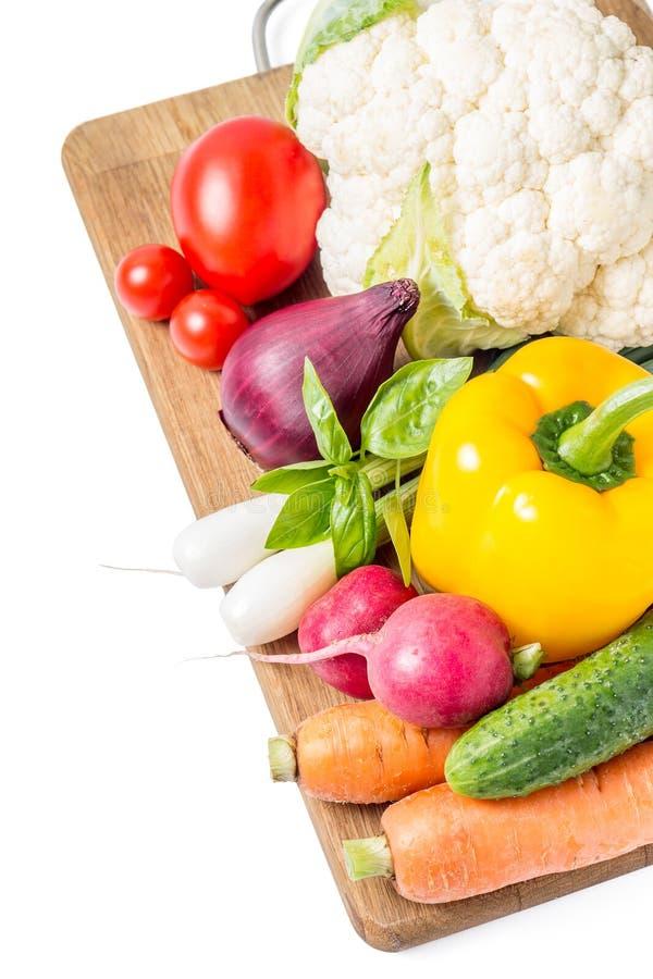 Verduras frescas en el tablero de madera aislado en blanco imagen de archivo libre de regalías