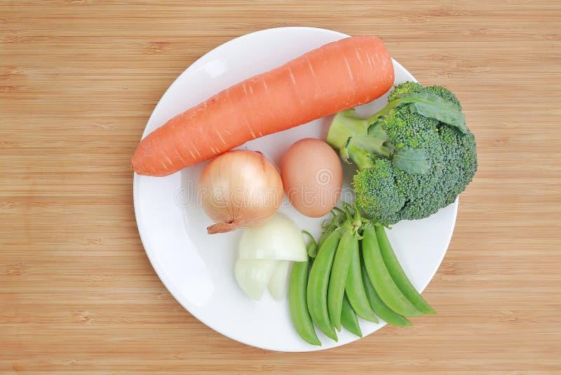 Verduras frescas en la placa blanca contra el bróculi, la zanahoria, el huevo, la cebolla y el guisante de olor de madera del fon fotografía de archivo libre de regalías