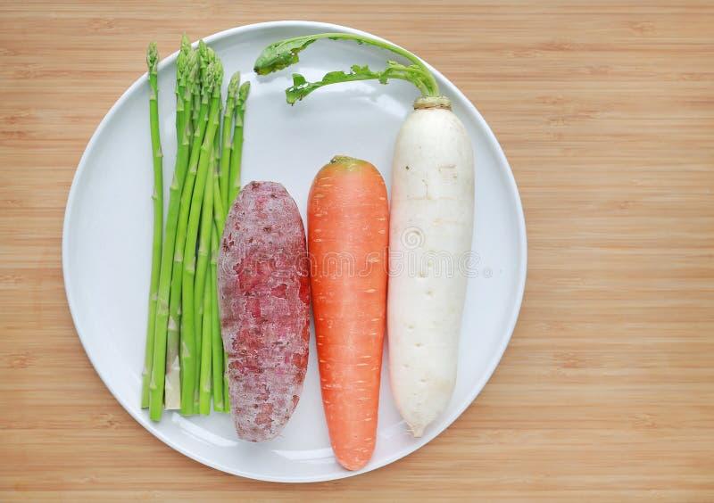 Verduras frescas en la placa blanca contra el espárrago de madera del fondo, la zanahoria, el rábano y la patata dulce imágenes de archivo libres de regalías