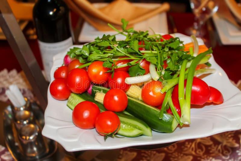 Verduras frescas en un plato en el restaurante: pepinos, tomates de cereza, cilantro, cebollas verdes, paprikas fotografía de archivo