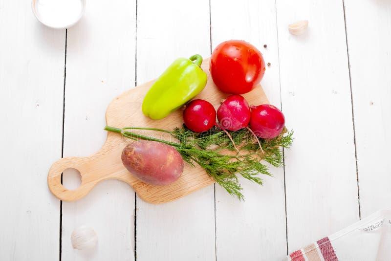 Verduras frescas en una tajadera - rábanos, patatas, eneldo, tomate, pimientas de dulce - fondo de madera ligero imagen de archivo