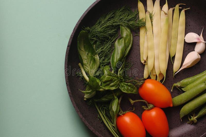 Verduras frescas orgánicas calabacín, tomate, espárrago, albahaca, eneldo, guisantes verdes, ajo en un sartén imagen de archivo