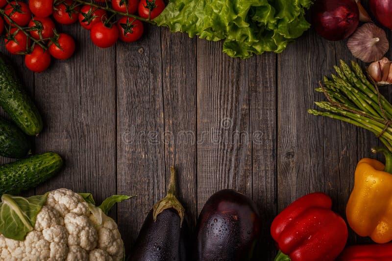 Verduras frescas para cocinar en fondo de madera oscuro foto de archivo