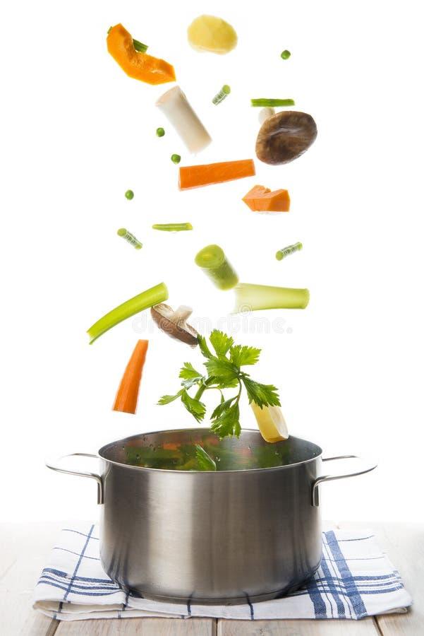Verduras frescas que caen en un pote aislado en un backgrou blanco imágenes de archivo libres de regalías