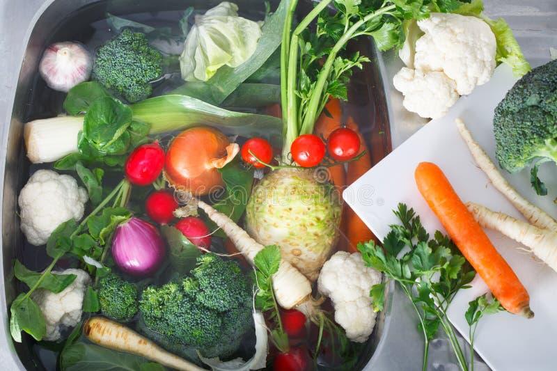 Verduras frescas que se lavan en fregadero de cocina imágenes de archivo libres de regalías