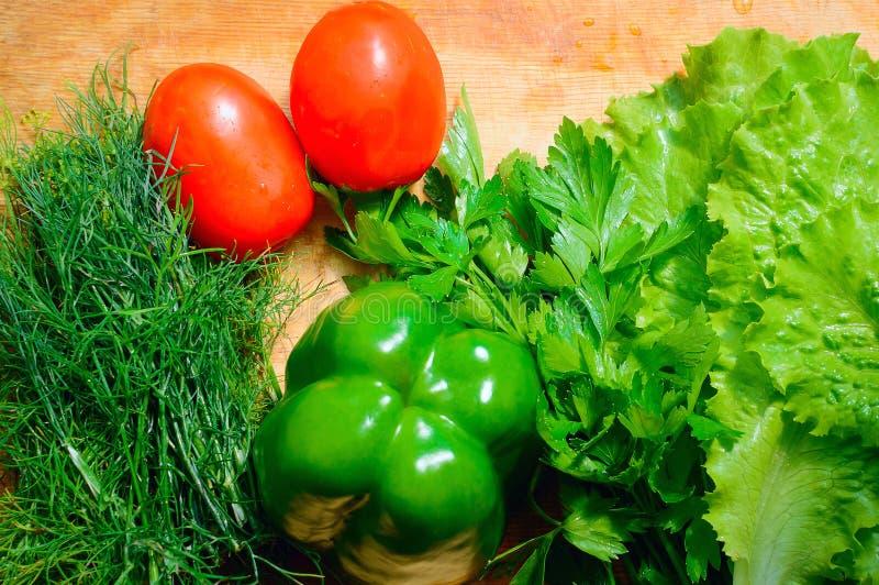 Verduras frescas: tomate, lechuga, eneldo, perejil, y paprika que miente en la tabla Alimento sano natural fotografía de archivo libre de regalías