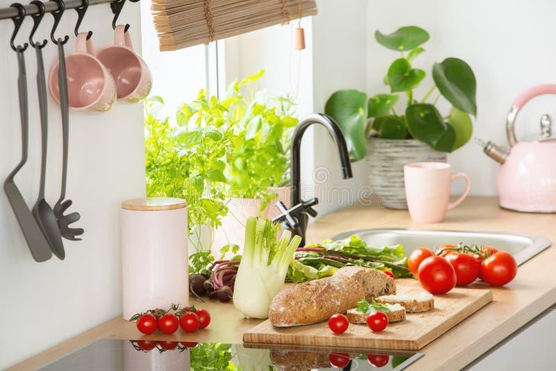 Verduras frescas y pan colocados en encimera en la foto real del interior de la cocina con la caldera y las tazas del rosa en col imagenes de archivo