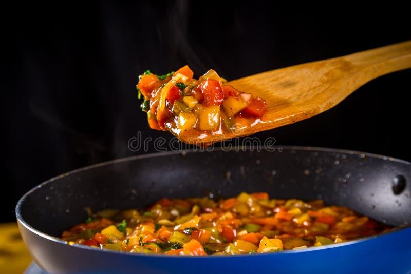 Verduras fritas en la espátula y el sartén foto de archivo